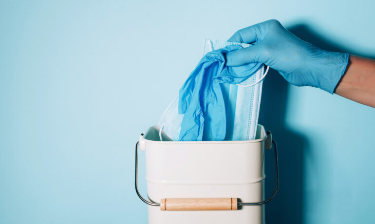 Hand in medical gloves throws medical mask into trash can on blue background. Quarantine over. Covid 19. Concept of coronavirus end. Banner with copy space. Stay safe. Health protection equipment.