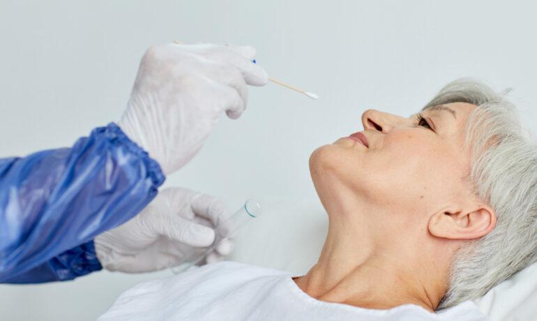 Unrecognizable medical worker wearing protective uniform taking senior woman's nasal swab for coronavirus test