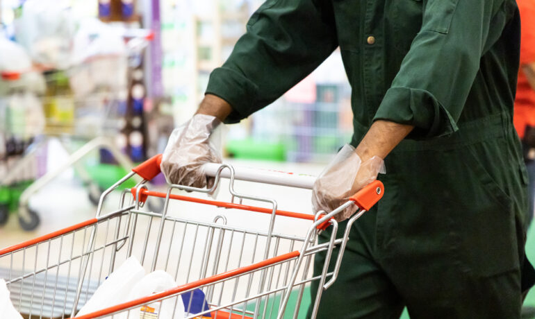 New normal lifestyle with shoppers put on disposable gloves in supermarket for protection against coronavirus in Malaysia